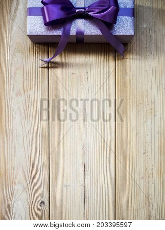 Birthday present with purple satin tape on wooden board. Holidays concept