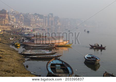 VARANASI INDIA - JANUARY 25 2017 : Morning view at holy ghats and wooden boats at the river ganges of Varanasi India