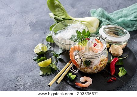 Rice noodles with shrimps and vegetables in jar fast lunch asian food with chopsticks asian chinese or thai food