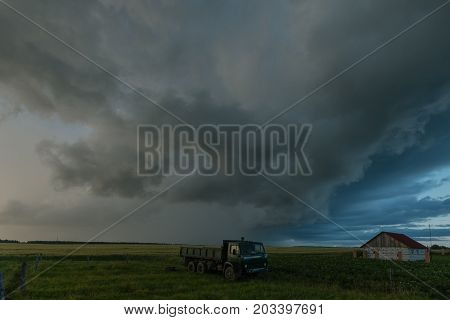 Scary gray clouds have tightened the sky in the field in which the kamaz and the house.