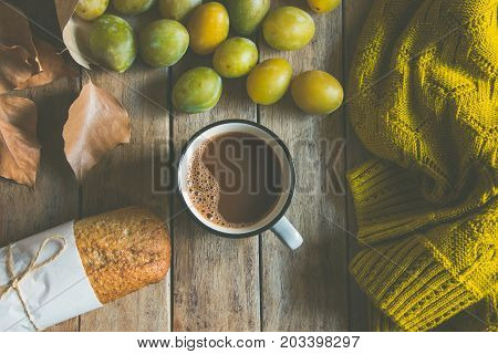 Cup of hot chocolate or cocoa whole grain rye bun scattered yellow and green plums in craft paper bag. Dry leaves knitted woolen sweater on plank wood background. Autumn fall top view cozy.