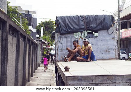 05 Aug 2017 Dumaguete Philippines: two workers on commercial truck platform. Low-paid work on truck. Streetlife of asian city. Poor people of developing country. Simple urban lifestyle. Smiling men