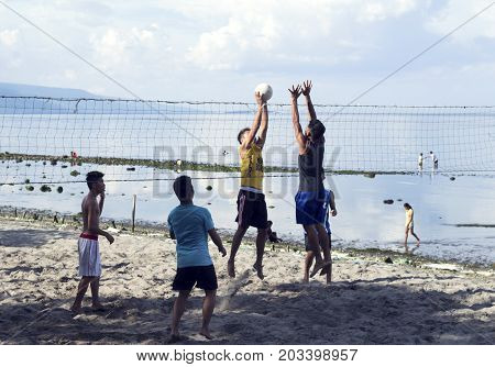 05 Aug 2017 Dumaguete Philippines: young boys playing beach volleyball by sea. Seaside landscape with active youngster. Summer seaside activity. Ball game playing children. Sand beach sport game