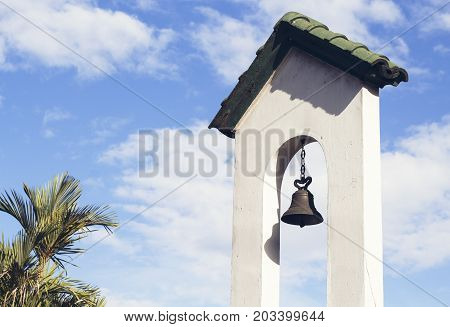 Church bell on church tower on blue sky background. Catholic church building. Catholic religious architecture detail. White stone tower with bell. Traditional religious building on tropical island