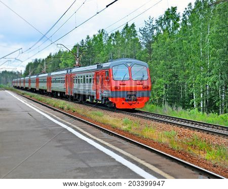 Electric train moving past empty railway platform near wood. Image can be used as background.
