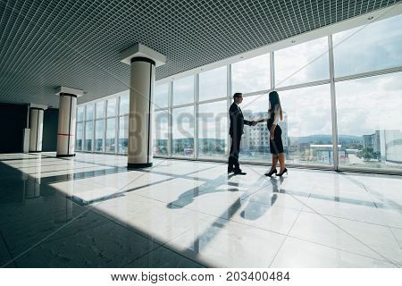 Businessman And Businesswoman Shaking Hands Together While Standing In Front Of Office Building Wind