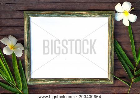Blank paper on wooden background flat lay. Natural rustic photo frame with blank place for text. Bamboo leaf and frangipani flower on table. Mockup top view. Wood frame with tropical floral decor