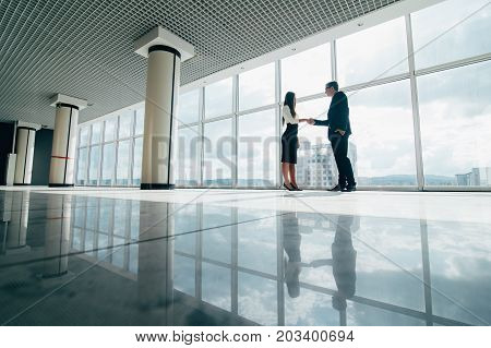Businessman And Businesswoman Shaking Hands In Office With Big Panoramic Windows