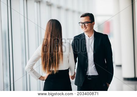 Businessman And Businesswoman Shaking Hands In Office With Big Panoramic Windows In Office Hall