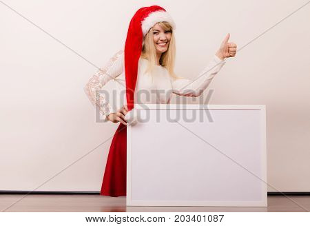 Happy woman in santa helper hat holding empty blank banner with copy space. Pretty girl in studio on gray. Christmas xmas advertisement.
