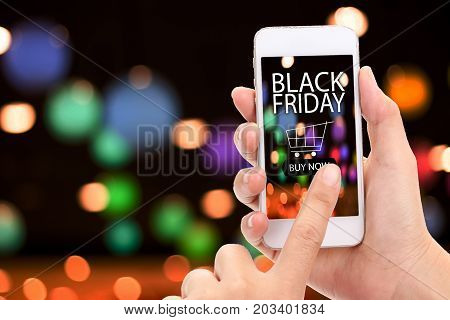 Black friday concept. Woman hand click BUY NOW on mobile with blur supermarket background Grocery online delivery concept.