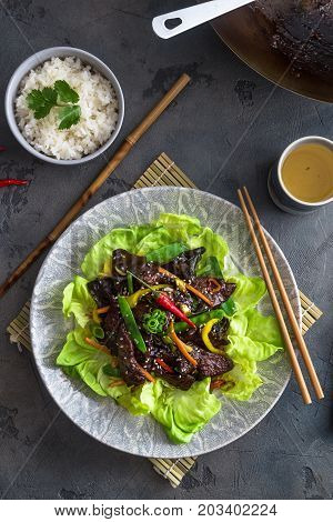 Asian stir fried chicken liver with bowl of rice and green tea, top view