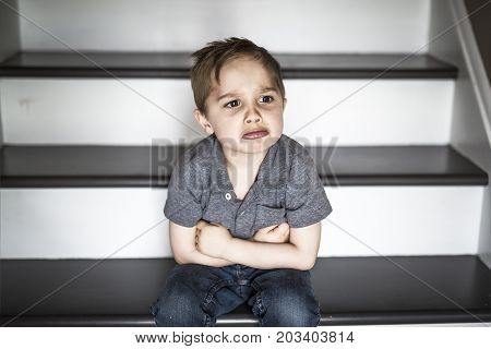 one sad little boy sitting on the stairs in house at the day time.