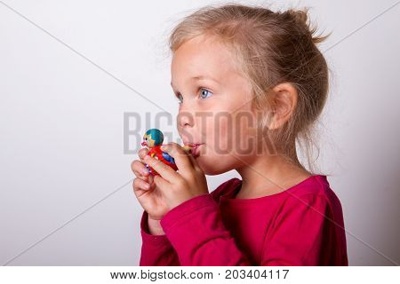 child blows into the whistle wooden whistle toy