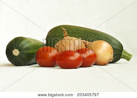 Several vegetables (zucchini onion bulbs and tomatoes) on a white background