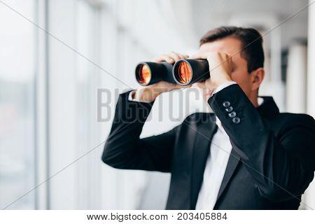 American Businessman Using Binoculars Look In Windows In Office