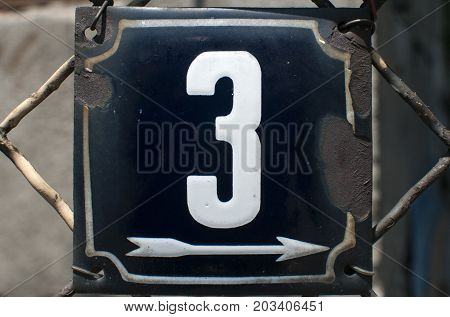 Weathered grunge square metal enameled plate of number of street address with number 3 closeup