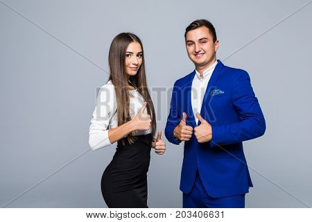 Two Confident Smiling Businesspeople In Formalwear Showing Thumbs-up On Gray Background