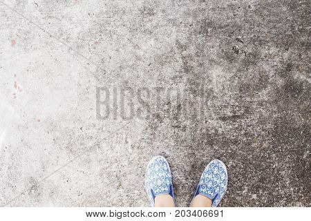 Woman's feet in walking shoes on asphalt road. Industrial concrete floor top view photo. Urban walk banner. Obsolete background texture. Grungy backdrop with slip-on. Shabby chic shoes on asphalt
