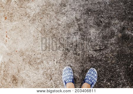 Woman's feet in walking shoes on asphalt road. Industrial concrete floor top view photo. Urban walk vintage banner. City footwear outdoors. Grungy backdrop with slip-on. Shabby chic shoes on asphalt