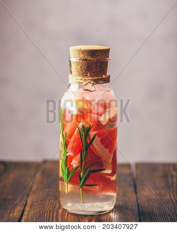 Bottle of Detox Water Infused with Sliced Raw Grapefruit and Fresh Springs of Rosemary. Vertical Orientation. Copy Space on the Top.