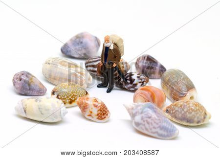Senior traveler and sea shells on white background. Aged backpacker and seashells collection. Tropical vacation for senior tourist. Colorful tropical shells. Miniature figurine of man on beach concept