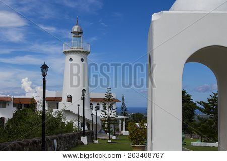 White lighthouse by rotunda in Greek architectural style. Tropical place resort with sea view. White gazebo and lighthouse summer park. Romantic wedding place. Decorative lighthouse on mountain top