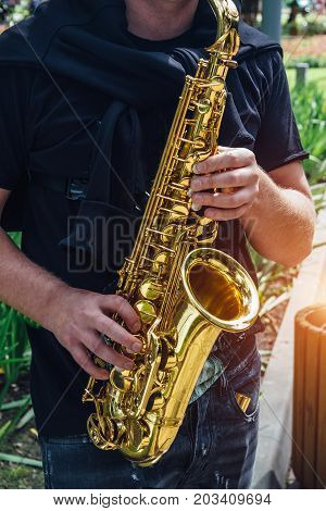 Close up of saxophone player's hands playing jazz music. Street saxophonist playing sax alto