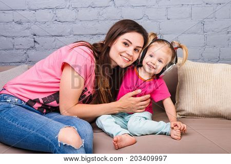 Mother And Daughter Of Two Years Listening To Music With Headphones On Their Head. Sit On The Couch