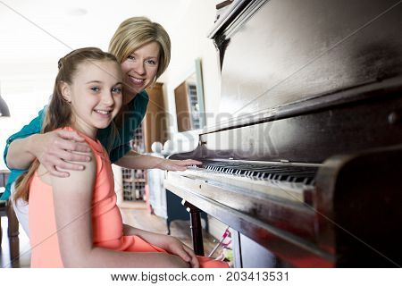 A Woman teaching little girl to play the piano.