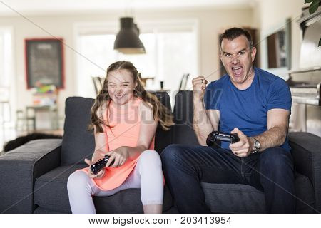 A Handsome father and his cute little daughter are playing game console and smiling while sitting on couch at home.