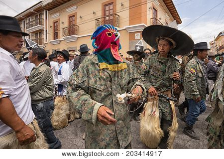 July 24 2017 Cotacachi Ecuador: indigenous kichwa men wearing a traditional mask on the street at Inti Raymi celebration