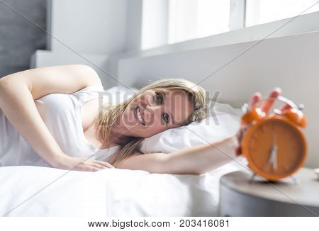 Happy woman waking up and turning off the alarm clock having a good day
