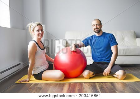 A Young couple doing exercise at home in living room.