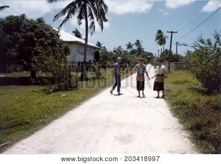 NUKU'ALOFA, TONGATAPU / TONGA - CIRCA 1990: Three young men pose for a photograph in an alley in Tonga's capital city.