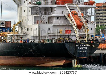 Labuan,Malaysia-Aug 30,2017:Freight shipping containers at the docks with a free fall lifeboat in Labuan island,Malaysia.A free fall lifeboat is a special form of a rescue boat on every commercial ship.
