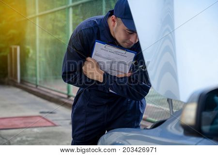 Mechanic repairman inspecting car Maintaining car records. Auto technician checking car engine holding paperwork for checkup inspector after fixing. Auto service concept.
