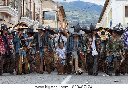 June 24 2017 Cotacachi Ecuador: indigenous young boy among people dancing in the street during summer solstice celebrations