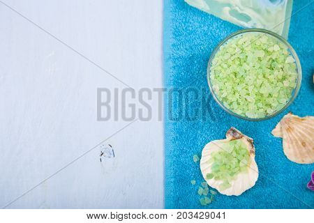 Spa treatments on a blue wooden table. Sea salt soap towel and orchid close-up.