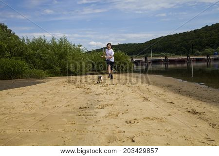 Boy And Dog Running In A Sandy Beach