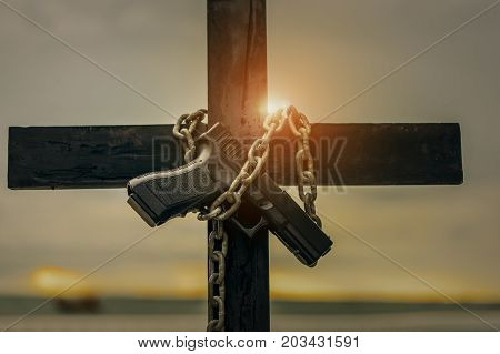 Cross holding gun with chain lock on prison the death concept.