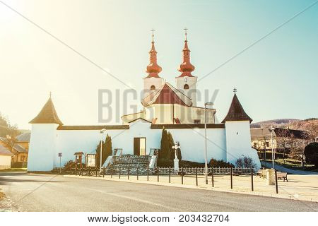 Roman catholic church in Divin village Slovak republic. Religious architecture. Yellow sun rays. Jesus Christ on the cross.