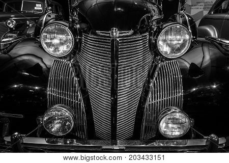 MAASTRICHT NETHERLANDS - JANUARY 08 2015: Radiator grill and headlamps of a full-size luxury car Cadillac Series 75 Imperial Sedan 1939 close-up. Black and white. International Exhibition InterClassics & Topmobiel 2015