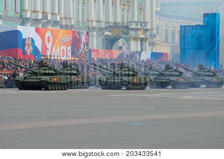 ST. PETERSBURG, RUSSIA - MAY 07, 2017: A column of the Russian tanks against the background of festive stands. A dress rehearsal of a parade in honor of the Victory Day