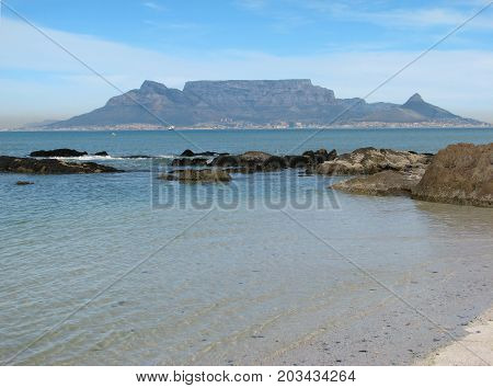 FROM BLOUBERG STRAND, CAPE TOWN, SOUTH AFRICA, WITH A VIEW OF TABLE MOUNTAIN IN TH BACK GROUND, AND THE CALM TURQUOISE WATERS OF THE ATLANTIC