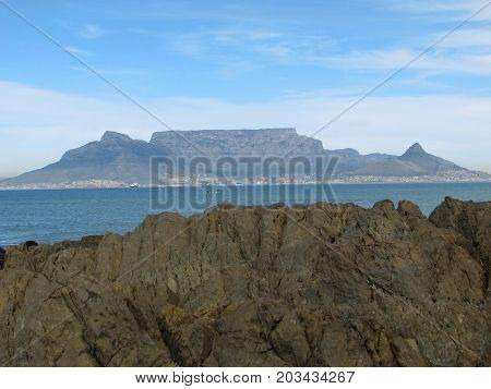 VIEW FROM BLOUBERG STRAND, CAPE TOWN, SOUTH AFRICA, WITH HUGE BOULDERS IN THE FORE GROUND AND TABLE MOUNTAIN IN THE BACK GROUND