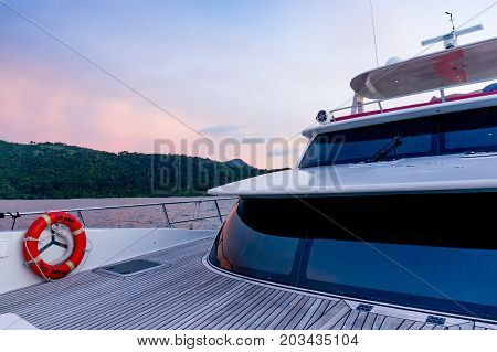 langkawi, Malaysia - 4th May 2017:Deck of a ship shot during the purple light of dusk. The wooden deck, beautiful curved glass and modern shape show the luxury and beauty of these modern ships