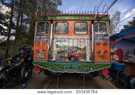 August 6 2017 Medellin Colombia: a colourful od bus called 'chiva' drives through the crowded street during the flower festival