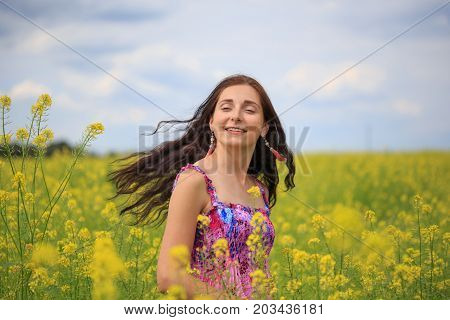 Woman With Flying Hair On Yellow Rape Field