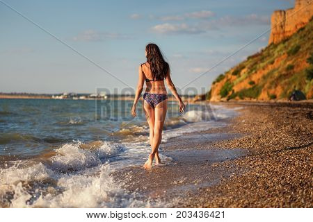 Slender Woman In Swimsuit Walks At Seacoast